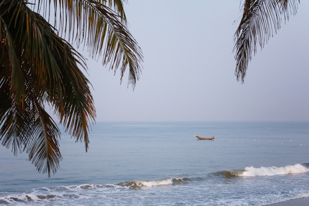 Varkala, India - February 09, 2016: fisherman standing and sighting fish in traditional wooden canoe boat on blue indian ocean during morning catch