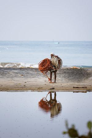 Varkala, India - February 09, 2016: Lonely Indian Fisherman carrying net ropes walking on the sand, reflection in backwaters of Odayam beach near Varkala, Kerala, India