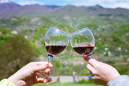 Toasting with two glasses of red wine Khvanchkara in the Georgian vineyard