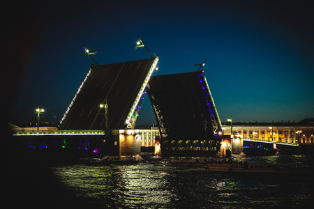 Classic symbol of St. Petersburg White Nights - a romantic view of the open Palace Bridge, which spans between - the spire of Peter and Paul Fortress