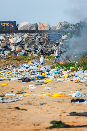 Kollam, India - February 14, 2016: A child girl plays in piles of trash while her mother burns it on the beach of Kollam, Kerala Editorial