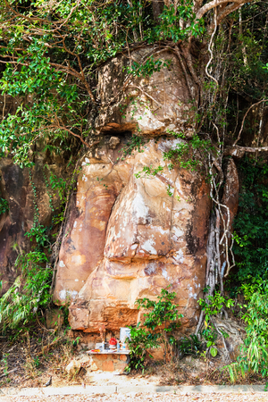 Stone face of Buddha by the Picturesque road in mountains of National park Bokor leading to Abandoned hotel Bokor Palace in Ghost town Hill station near Kampot. Cambodia in the clouds Stock Photo