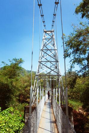Kandy, Sri Lanka - 5 February 2017: Suspension bridge with tourists in Royal Botanical King Gardens, Peradeniya, Sri Lanka, locates near Kandy