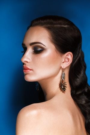 Glamour Portrait of Beautiful brunette Woman with Evening Make-Up and Hollywood Hairstyle at blue Background. Fashion Shiny Highlighter on Skin, Sexy Volume lips and earings and Dark Smokey Eyes. Reklamní fotografie