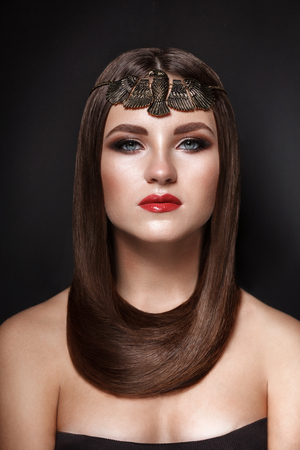 brunette straight glossy hair beauty ethnic woman portrait on dark grey background. Hair wrapped around the neck like a scarf. head decoration in the form of a golden eagle in the Egyptian style