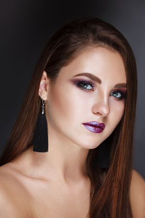 Beautiful brunette woman with long, healthy , straight and shiny hair. Hairstyle loose hair. Nude storng colorful purple lips make up.