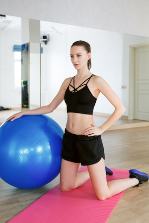 Woman doing pilates exercises with a blue fitball and doing exercises with dumbbells. wearing black top and ahorts in gym with mirrors
