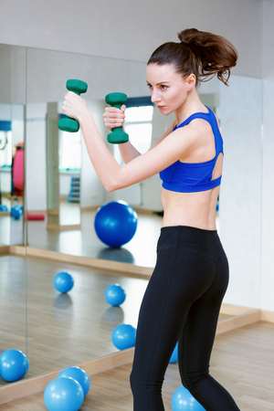 Woman standing near a blue fitball and doing exercises with dumbbells. wearing blue top and black leggins Reklamní fotografie