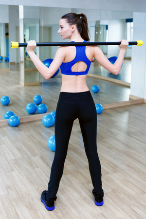 Woman standing near a blue fitball and doing exercises with bodybar. wearing blue top and black leggins Reklamní fotografie