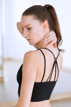 Woman posing doing exercises in fitness club wearing black top with stripes straps on her back in gym