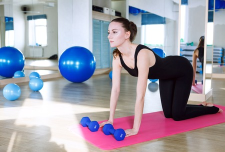 Woman sitting on pink ypga matt and doing exercises in fitness club gym, wearing black overall jumpsuit Reklamní fotografie