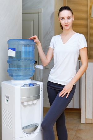 Woman, 20s, caucasian, standing at water cooler wearing sportwear after gym workout