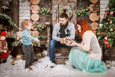 Christmas family of three persons mother father and son two year old boy and fir tree with gift boxes in new year winter wooden decorated background.