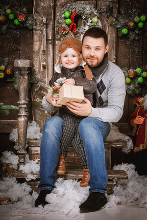 Christmas happy family of two persons happy father gives a gift to his two year old boy son in new year winter wooden decorated background with gift boxes and fir tree.