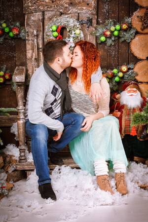 Christmas family of two persons mother father young couple kissing near fir tree with gift boxes in new year winter wooden decorated background.