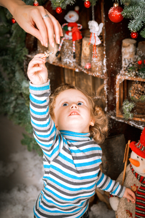 Little two year old boy dressed in blue sweater decorates christmas tree in wooden vintage decorations. Plays with gifts and snow Reklamní fotografie