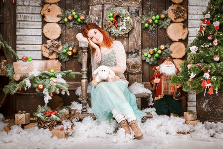 Christmas happy woman posing in fir tree with gift boxes in new year winter wooden decorated background. Reklamní fotografie