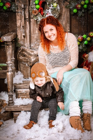 Happy red hair mother and two years old son boy are sitting in christmas decorations wooden loft style playing with the boy Reklamní fotografie