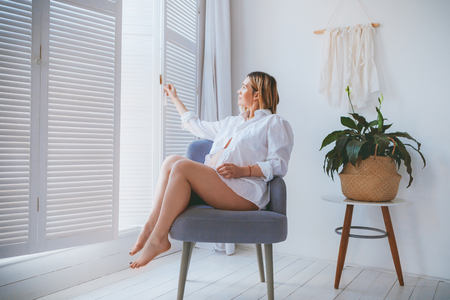 Pregnant mothercare lifestyle concept, Bob hairstyle blond woman health care. white light interior, mother sitting on the grey armchair in the room with blinders and wooden floor. green plant in the corner