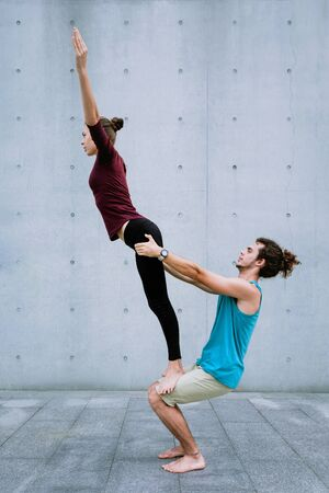 Male and female couple practicing acro yoga outdoors on grey wall background. Acroyoga concept for beginners. Pair yoga. Yoga flexibility class workout. Reverse tight stand asana