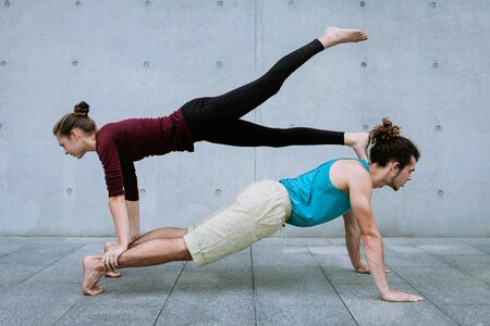 Male and female couple practicing acro yoga outdoors on grey wall background. Acroyoga concept for beginners. Pair yoga. Yoga flexibility class workout. Plank on Plank asana with leg up Reklamní fotografie