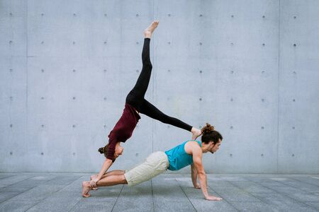 Male and female couple practicing acro yoga outdoors on grey wall background. Acroyoga concept for beginners. Pair yoga. Yoga flexibility class workout. downward dog and plank asana.