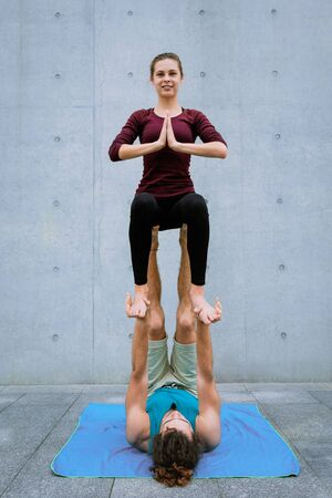Male and female couple practicing acro yoga outdoors on grey wall background. Acroyoga concept for beginners. Pair yoga. Yoga flexibility class workout. Throne pose asana