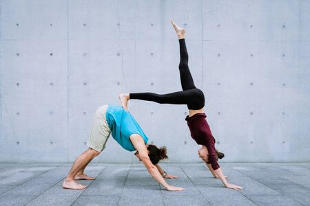 Male and female couple practicing acro yoga outdoors on grey wall background. Acroyoga concept for beginners. Pair yoga. Yoga flexibility class workout. Downward dog and handstand.