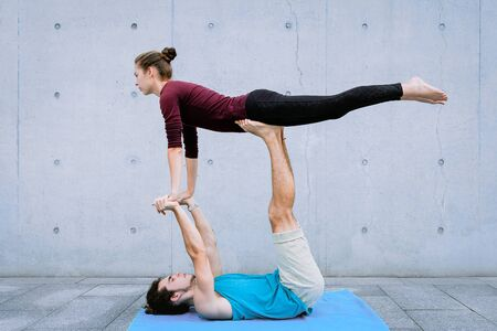 Male and female couple practicing acro yoga outdoors on grey wall background. Acroyoga concept for beginners. Pair yoga. Yoga flexibility class workout. Front Bird pose asana