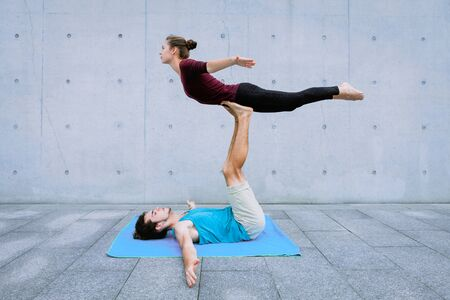 Couple practicing acro yoga outdoors on grey wall background. Acroyoga concept for beginners. Pair yoga. Yoga flexibility class workout. Front free Bird pose Reklamní fotografie