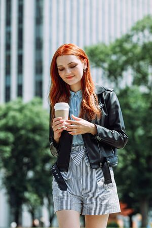Happy young trendy red hair woman wearing black leather jacket and shorts, drinking take away coffee and walking in an urban city. City walk lifestyle concept.