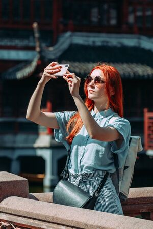 Red hair female tourist wearing blue shirt and sunglasses using mobile phone screen for picture with smartphone of Yuyuan Garden in Shanghai, china. Asia tourism travel. People taking photos during vacation. Travel lifestyle concept Reklamní fotografie