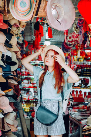 happy young caucasian red hair woman wearing blue shirt and black purse tries on a hat while shopping at a store that sells wicker hats in Asian touristic market in China. travel shopping lifestyle concept 版權商用圖片