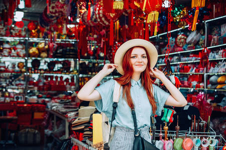 happy young caucasian red hair woman wearing blue shirt and black purse tries on a hat while shopping at store sells wicker hats in Asian touristic market in China. travel shopping lifestyle concept