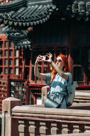 Red hair female tourist wearing blue shirt and sunglasses using mobile phone screen for picture with smartphone of Yuyuan Garden in Shanghai, china. Asia tourism travel. People taking photos during vacation. Travel lifestyle concept 版權商用圖片