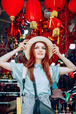 happy young caucasian red hair woman wearing blue shirt and black purse tries on a hat while shopping at a store that sells wicker hats in Asian touristic market in China. travel shopping lifestyle concept Reklamní fotografie