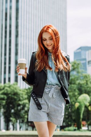 Happy young trendy red hair woman wearing black leather jacket and shorts, drinking take away coffee and walking in an urban city. City walk lifestyle concept. 版權商用圖片 - 145580721