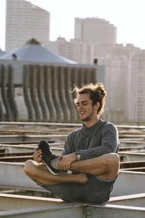 Positive young european man crossing legs in lotus pose croosed legs on blurry urban residential building city background. Urban yoga concept. Relaxation in city life