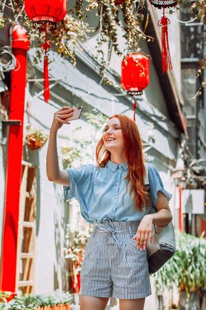 Red hair tourist uses mobile phone for picture with smartphone of Yuyuan Garden street with red lanterns in Shanghai, china. Asia tourism travel. People taking photos during vacation lifestyle concept Reklamní fotografie - 145580724