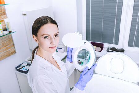 Female woman doctor beautican holding magnifier before the procedure in cabinet office 版權商用圖片