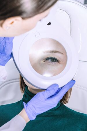 Female woman doctor beautician is analysing skin through magnifier on female patient face before the procedure in cabinet office. Eye close up. Anti-aging Procedures concept