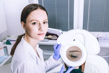 Female woman doctor beautician is analysing skin through magnifier on female patient face before the procedure in cabinet office. Anti-aging Procedures concept