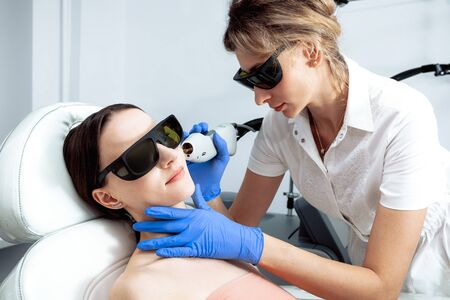Skin Care. Young Woman Receiving Facial Beauty Treatment, Removing Pigmentation At Cosmetic Clinic. Intense Pulsed Light Therapy. IPL. Rejuvenation, Photo Facial Therapy. Anti-aging Procedures. Laser cosmetology concept blond doctor and patient wearing black protection glasses