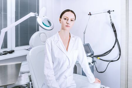 Female woman doctor beautican holding magnifier before the procedure in cabinet office. Laser IPL equipment