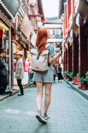 Female red hair tourist waliking in Chinese district in Shanghai, china. Asia tourism travel. Woman wearing travel backpack, sneakers and blue shirt and shorts in Tianzifan district Reklamní fotografie