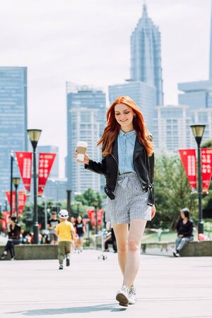 Happy young trendy red hair woman wearing black leather jacket and shorts, drinking take away coffee and walking in an urban city. City walk lifestyle concept. Reklamní fotografie - 146104484