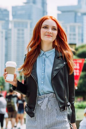 Happy young trendy red hair woman wearing black leather jacket and shorts, drinking take away coffee and walking in an urban city. City walk lifestyle concept. 版權商用圖片 - 146104485