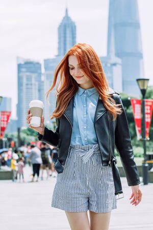 Happy young trendy red hair woman wearing black leather jacket and shorts, drinking take away coffee and walking in an urban city. City walk lifestyle concept. 版權商用圖片 - 146104486