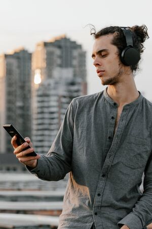 Man sitting on the rooftop and listening to the music application in wireless black headphones and checking his smartphone wearing a grey shirt and blue jeans shorts, curly hair collected in high ponytale . Background of residential buliding cityscapes. Urban lifestyle concept