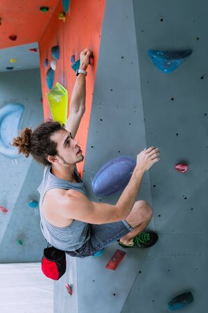 Urban concept of man with curly long hair, tied in a ponytail, is training at the city artificial red and blue climbing wall using talcum powder, wearing a bag for climbing without insurance equipment 版權商用圖片 - 146104498